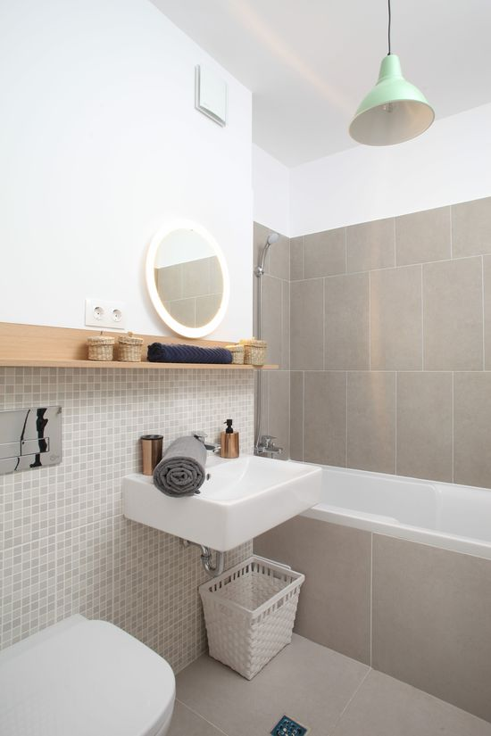 Cromatica în culori neutre completată de elemente din lemn a fost aleasă și pentru baie. Plăcile ceramice provin de la Delta Studio, iar etajera și accesoriile din jurul său au fost cumpărate de la IKEA. Foto: Sorin Iacob